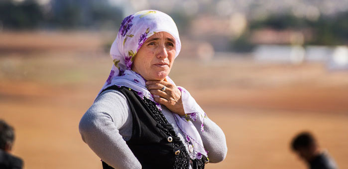 A Kurdish refugee woman from Kobani stands on a hill which overlooks Kobani, Syria, near the Turkish town of Suruc, at the Turkey-Syria border. ©Giannis Papanikos (Shutterstock)